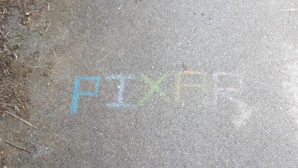 En el camino asfaltado hay una pintada, cada letra de un color, que se puede leer PIXAR