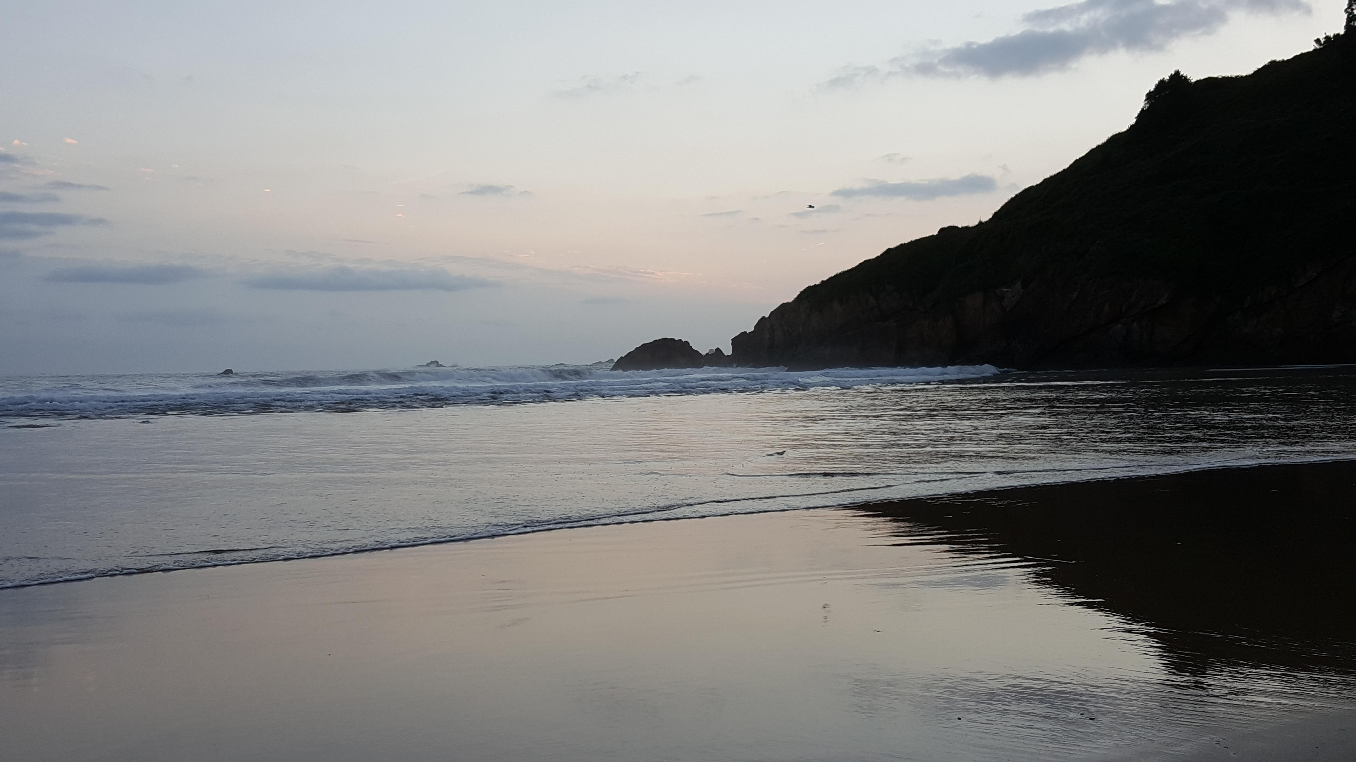 En la playa anochece, la mar se retira, el monte que se alza a la orilla y se refleja en la arena