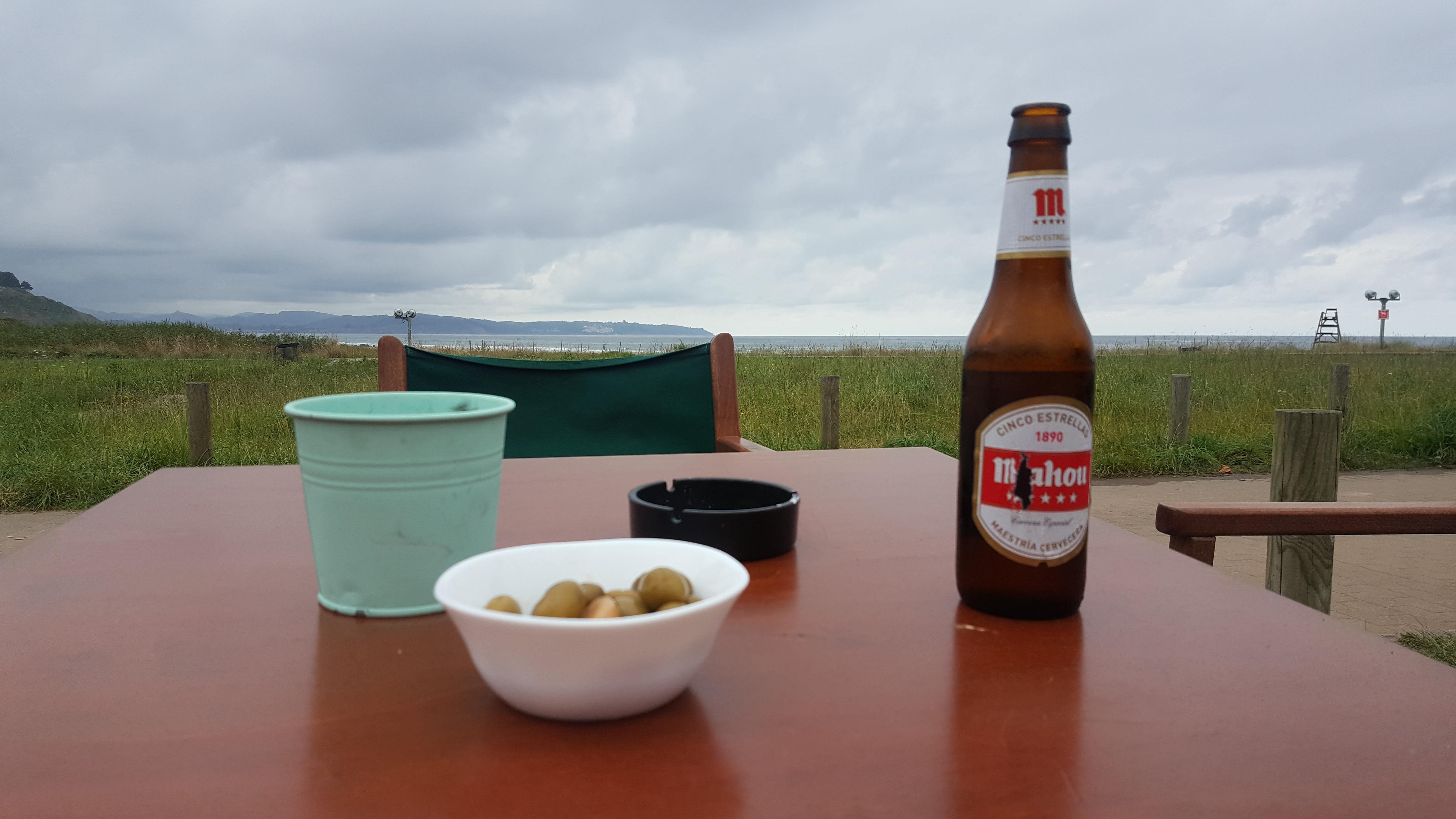 Sentado frente a una mesa. Sobre la mesa una cerveza fresca, un cuenco con aceitunas verdes y continuación, en el horizonte se divisa el mar bajo un cielo cubierto de nubes con distintos grises